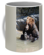 Grizzly Bear Licking His Paw While Seated In A Muddy River Coffee Mug