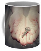 Key In Woman's Hand In Gesture Of Giving. Concept Of Success In Live, Business Solution, Real Estate Etc Coffee Mug