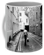 Man Walking With Shopping Bag Down Narrow English Street Coffee Mug