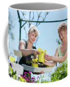 Mature Gardener Helps Senior Client With Flowers Coffee Mug
