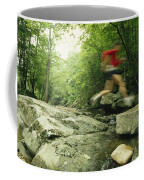 Panned View Of Man Leaping Over Rocky Coffee Mug by Skip Brown