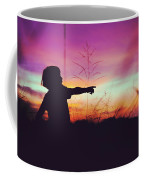 Silhouette Of A Playful Boy Pointing With Finger In The Field During Beautiful Sunset Coffee Mug