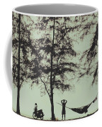 Silhouette Of A Young Men With Crossed Hands Above His Head Camping Hammocking In The Nature Coffee Mug