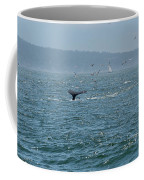 A Whale's Tail Above Water With Sail Boat In The Background Coffee Mug by PorqueNo Studios