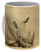 Resting Rhinoceros With His Head Down In A Sandy Area Coffee Mug