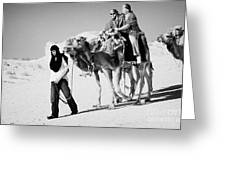 bedouin guide in modern clothing leads british tourists riding camels and wearing desert clothes into the sahara desert at Douz Tunisia Greeting Card