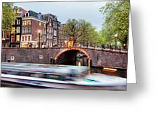 Canal Bridge And Boat Tour In Amsterdam At Evening Greeting Card