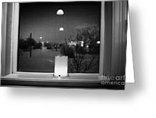 candle in the window looking out over snow covered scene in small rural village of Forget Saskatchew Greeting Card