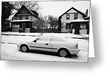 car covered in snow parked by the side of the street in front of residential homes caswell hill Sask Greeting Card by Joe Fox