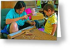 Child Watches As Mom Works In Teak Wood Carving Shop In Kanchanaburi-thailand Greeting Card