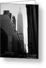 empire state building shrouded in mist in amongst dark cold buildings on 33rd Street new york city Greeting Card by Joe Fox
