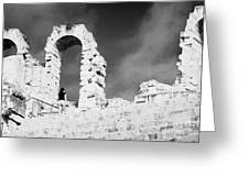 Female Tourist Walks Up The Stepped Seating Area Towards Ruined Archways Of The Old Roman Colloseum At El Jem Tunisia Greeting Card