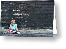 Girl Sitting On Ground Next To Brick Wall Greeting Card