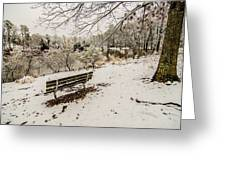Park Bench In The Snow Covered Park Overlooking Lake Greeting Card