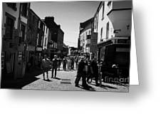 pedestrians walking down closed pedestrian area of quay street on sunny sunday afternoon Galway city Greeting Card