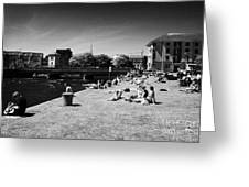 people enjoying the sunshine on the quay next to the corrib river on a sunday afternoon Galway city  Greeting Card