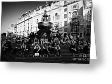 tourists and visitors sit on the steps of the eros statue in picadilly circus London England UK Greeting Card