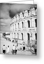 Tourists Walk Down Steps Towards  The Main Entrance Of The Old Roman Colloseum Against Blue Cloudy Sky El Jem Tunisia Vertical Greeting Card