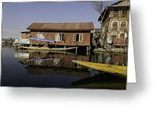 Yellow Shikara In Front Of A Run Down Area Of Houses In The Dal Lake Greeting Card