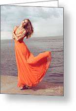 Young Woman In Orange Dress Flying In The Wind At Sea Shore Greeting Card by Oleksiy Maksymenko