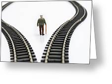 Figurine Between Two Tracks Leading Into Different Directions Symbolic Image For Making Decisions. Greeting Card by Bernard Jaubert