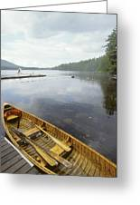 A Canoe Floats Next To A Dock Greeting Card
