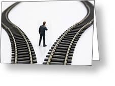 Figurine Between Two Tracks Leading Into Different Directions  Symbolic Image For Making Decisions Greeting Card by Bernard Jaubert