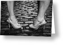 Two Young Women Wearing High Heeled Shoes And Fake Tan On Cobblestones On A Night Out Greeting Card by Joe Fox