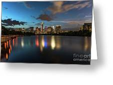 Clouds Roll Over The Austin Skyline As The Neon Reflects In The Glass-like Waters Of Lady Bird Lake Greeting Card