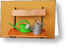 A Watering Can Of  Aluminium And A Plastic One Laid On Wooden Bench Greeting Card