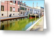 boat in a canal of the colorful italian village of Comacchio in  Greeting Card