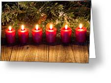 Glowing Red Candles With Snow Covered Evergreen Branch On Rustic Greeting Card