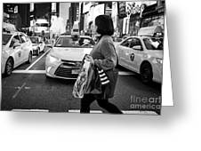 woman crossing crosswalk in front of yellow cabs in the evening in Times Square New York City USA Greeting Card