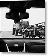 driving behind combine harvester on road in Saskatchewan Canada Metal Print