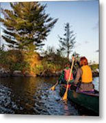 A Young Couple Paddles A Canoe On Long Metal Print