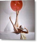 A Model Balancing A Red Ball On Her Feet Metal Print