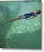 A Model Floating In A Swimming Pool Metal Print