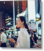 Beautiful Asian woman using mobile phone while crossing road in busy downtown city street at night Metal Print