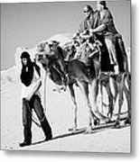 bedouin guide in modern clothing leads british tourists riding camels and wearing desert clothes into the sahara desert at Douz Tunisia Metal Print
