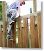 Boy Climbing Over Wooden Fence Metal Print