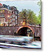Canal Bridge And Boat Tour In Amsterdam At Evening Metal Print