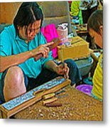 Child Watches As Mom Works In Teak Wood Carving Shop In Kanchanaburi-thailand Metal Print
