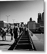 commuters and city workers cross london bridge over the river thames in the morning central London England UK Metal Print