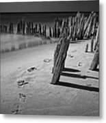 Footprints In The Sand Among The Pilings Metal Print