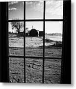 looking out through door window to snow covered scene in small rural village of Forget Metal Print