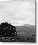 mound of Turf peat cut in a peat bog in front of mountains in Connemara County Galway Metal Print