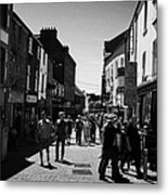 pedestrians walking down closed pedestrian area of quay street on sunny sunday afternoon Galway city Metal Print