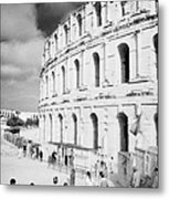 Tourists Walk Down Steps Towards  The Main Entrance Of The Old Roman Colloseum Against Blue Cloudy Sky El Jem Tunisia Vertical Metal Print