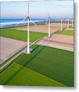 Wind turbines lined up along coast towards industrial area Metal Print