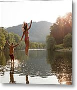 Young Couple Jumping Into River Metal Print